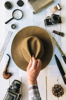 Traveler hand taking hat from table with map