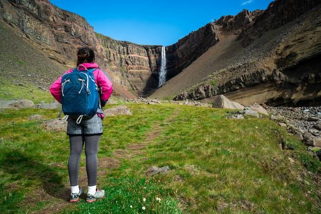 Traveler hiking at hengifoss waterfall, iceland.