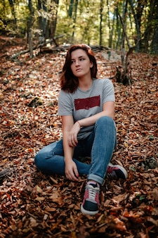 가 숲에 혼자 서있는 여행자 hipster 여자. 추운 날씨, 가을 색