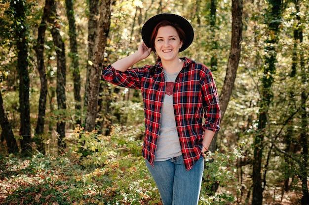 秋の森の中で黒い帽子と市松模様のシャツで一人で立っている旅行者の流行に敏感な女性。寒い天気、秋の色