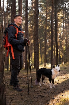 Traveler and his dog walking in the woods