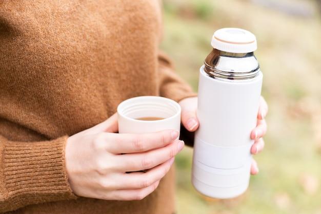 Путешественник с чашкой чая или кофе и термосом в осеннем лесу.