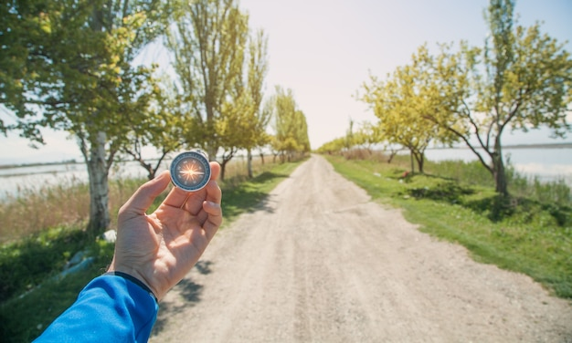Traveler holding compass in road background.