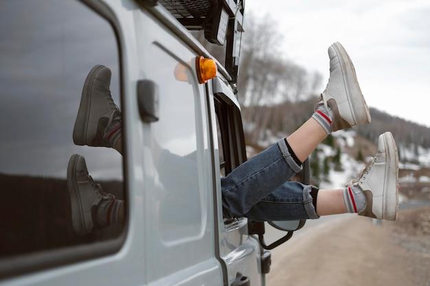 창 밖으로 다리를 들고 여행자를 닫습니다.