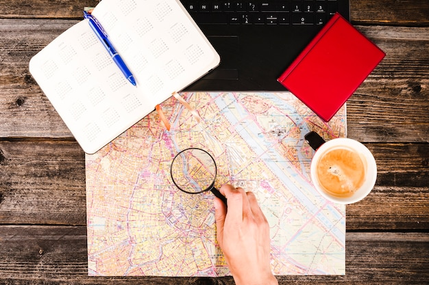 Traveler holding magnifying glass over map besides coffee and diary on table