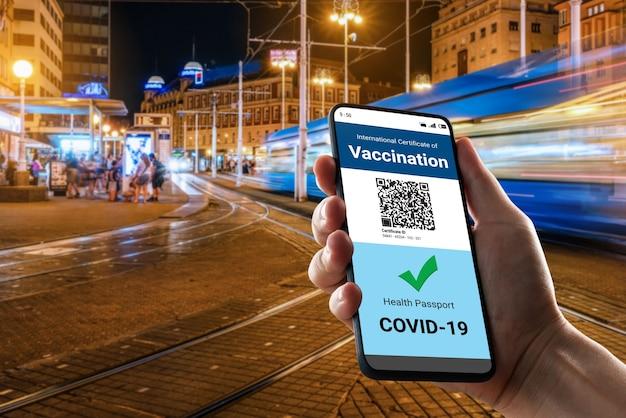여행자는 covid 19 예방 접종 상태를 보여주는 백신 여권 인증서를 보유하고 있습니다.
