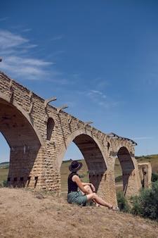 검은 모자를 쓴 여행자는 여름에 파괴 된 오래된 돌 다리 옆에 앉아 있습니다.
