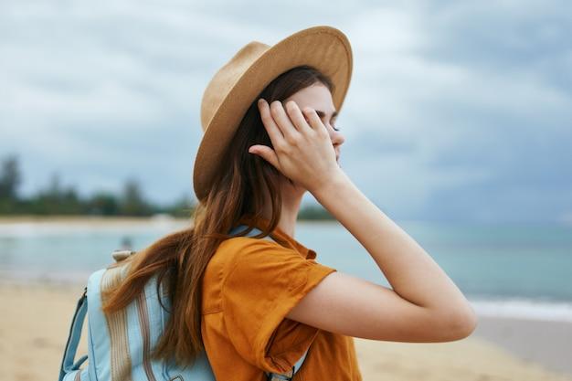 海の近くの島でバックパックを持って休む帽子をかぶった旅行者
