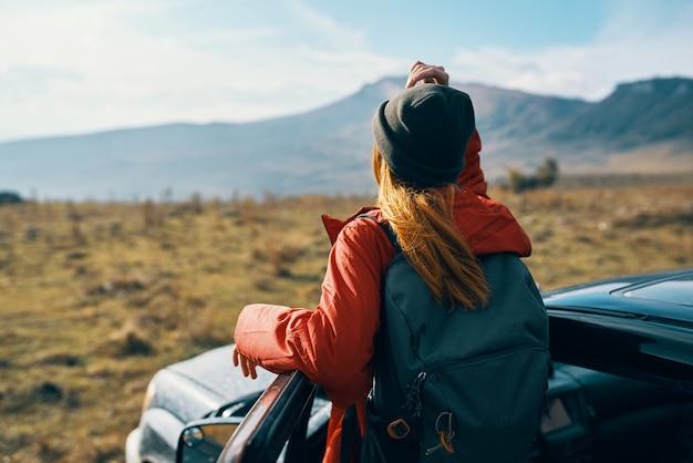 自然の中で車のドアの近くにバックパックをかぶった帽子をかぶった旅行者。高品質の写真