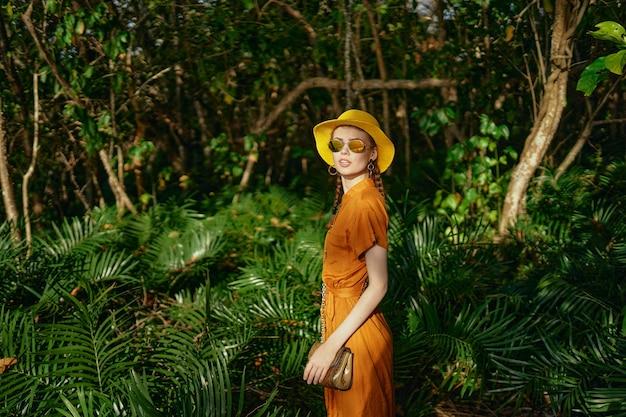 정글에서 sundress와 노란 모자의 여행자