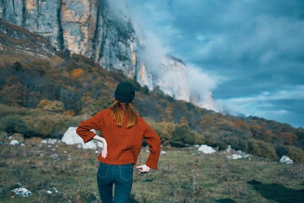 秋の山の屋外風景青空高岩モデルのセーターの旅行者