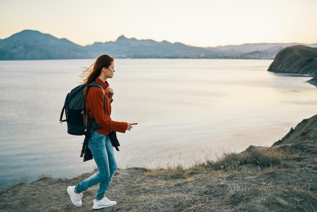 海の近くのビーチで、ジーンズとスニーカーのバックパックを持つセーターを着た旅行者