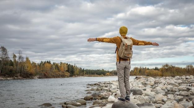 여행자는 해안에 큰 돌이 있는 빠른 강 옆에 팔을 뻗고 서 있습니다.