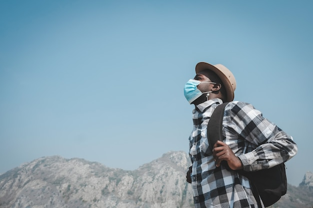 旅行者は防毒マスクを着用し、山を旅しています