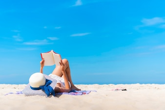 Traveler laying and reading a book at the tropical beach on summer vacation