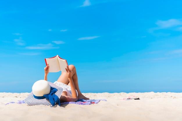 Путешественник кладет и читает книгу на тропическом пляже на летних каникулах
