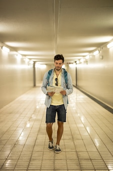 Путешественник смотрит на карту в подземном переходе