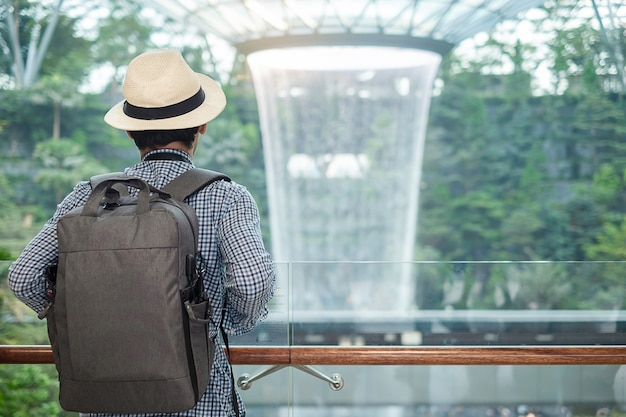 Traveler looking to beautiful rain vortex at jewel changi airport