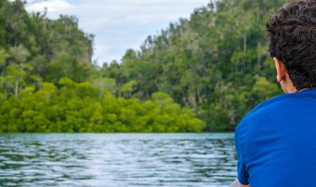 ワリカフホームステイ、カブイベイ、パッセージの近くのマングローブジャングルを眺める旅行者。ガム島、西パプア、ラジャアンパット、インドネシア。