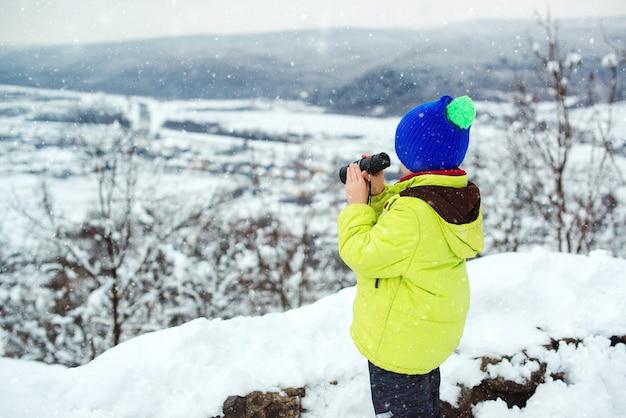 双眼鏡で遠くを見ている旅行者。冬の自然で幸せな子供。