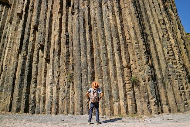 Путешественник смотрит на захватывающие дух базальтовые колонны высотой 50 метров в ущелье гарни армения
