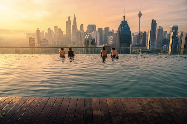 Traveler looking view skyline kuala lumpur city in swimming pool in kuala lumpur, malaysia