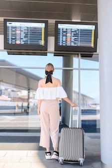 Путешественник смотрит на знак прибытия поезда