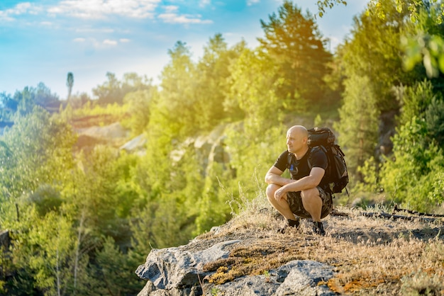 A traveler looks at the landscape around himself at the top of the cliff in the summer in warm weather.