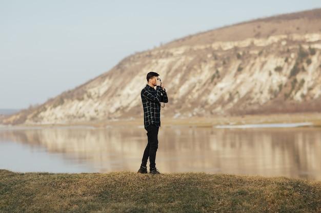 旅行者は旅行中に山のレトロなカメラで写真を撮る