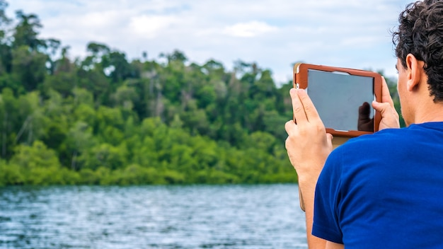 ワリカフホームステイ、カブイ湾、パッセージの近くでマングローブのガジェットを使って写真を作る旅行者。ガム島、西パプア、ラジャアンパット、インドネシア