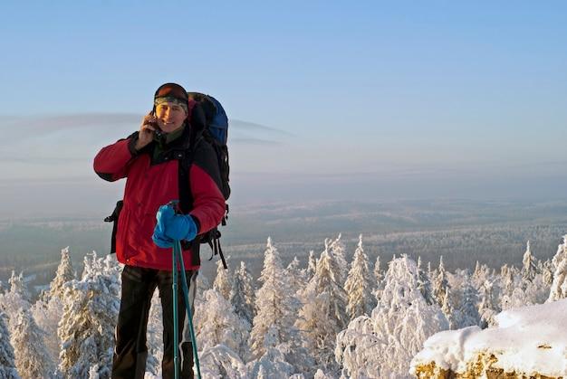 冬の風景を背景に携帯電話で話している山の旅行者の男