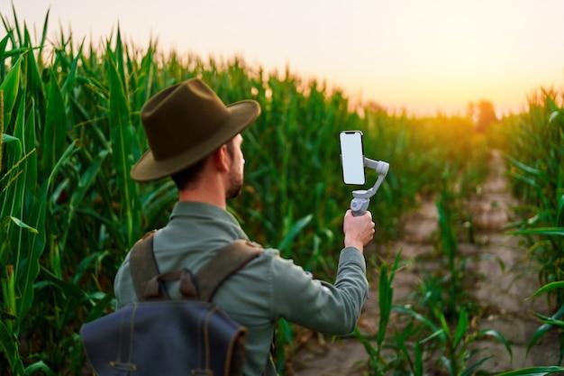 흰색 빈 화면 모형이 있는 전자 수동 전화 안정기 짐벌이 있는 여행자 남자 백패커 블로거는 셀카를 찍고 야외에서 비디오 블로그를 촬영합니다.