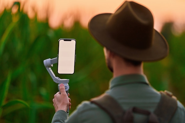 Traveler man backpacker blogger with electronic manual phone stabilizer gimbal with white blank screen mockup takes a selfie and shoots video blog outdoors