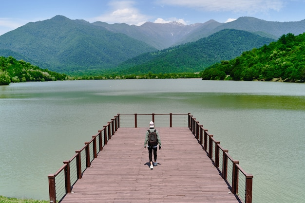Traveler man backpacker standing alone on pier and staring at lake and mountains. enjoying beautiful freedom moment life and serene quiet peaceful atmosphere in nature. back view