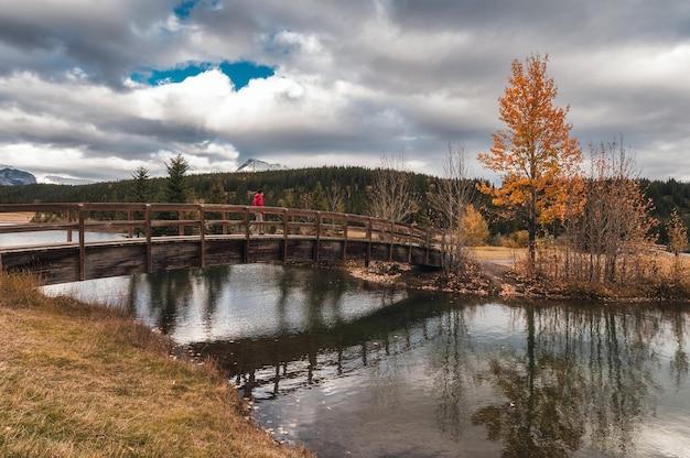 Путешественник пересекает деревянный мост на озере в осеннем лесу у каскадных прудов, национальный парк банф, канада