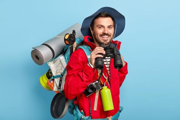 旅行者の男性はバックパックを持って歩き、旅行に必要なものを運び、双眼鏡で見て、嬉しそうに見え、カジュアルな服を着ています