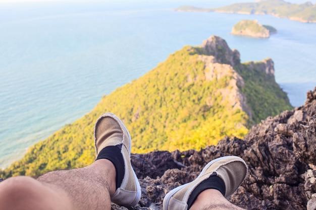 Traveler man hiking canvas shoesnear  ocean on nature