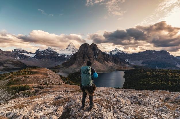 Путешественник, идущий на пик нубле с горой ассинибойн и озером в провинциальном парке, британская колумбия, канада