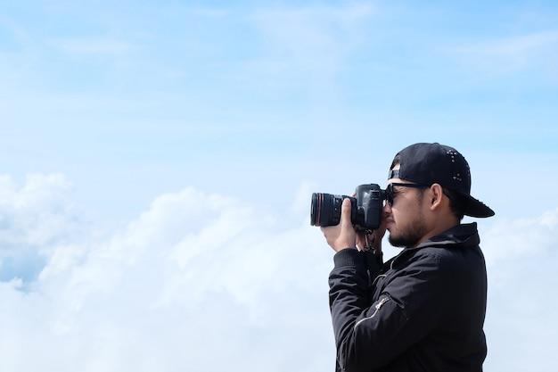 Путешественник мужчина держит камеру, фотографирует красивый пейзаж облачного фона