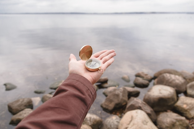 A traveler man holds a compass in his hand, standing on a stone beach.