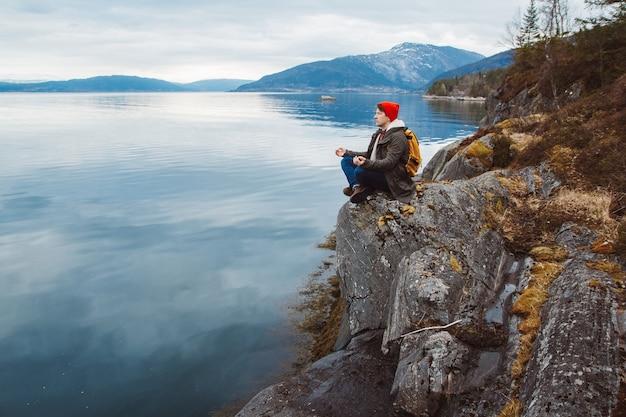 Путешественник в медитативной позе сидит на скалистом берегу на фоне горы и озера