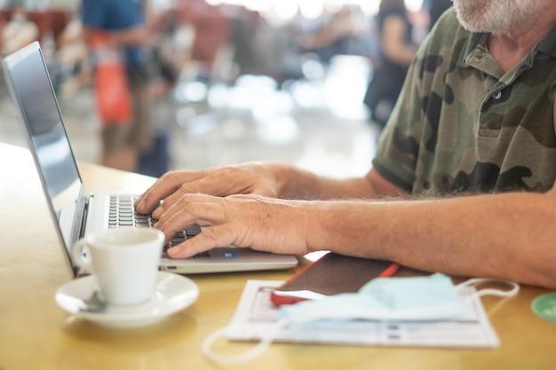 搭乗を待っている空港の旅行者の男性は、ラップトップコンピューター、シニアブロガーの在宅勤務、キーボードでの作業を待っています
