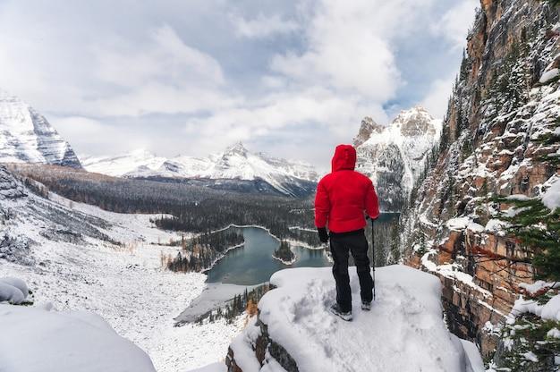 Путешественник в красном зимнем пальто стоит и смотрит на заснеженные горы и озеро с пика плато опабин в национальном парке йохо, канада