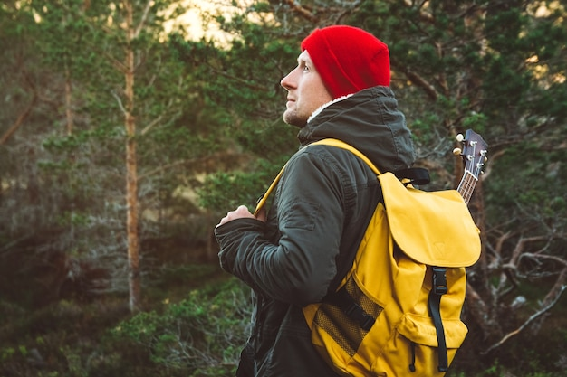 여행자 남자가 노란 배낭에 기타를 들고 숲 한가운데 있는 흔적에 서 있다