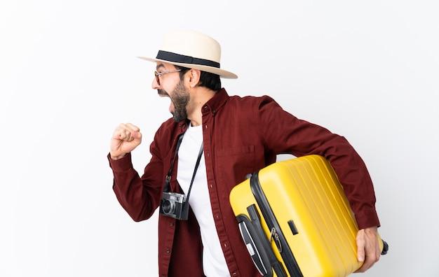 高速を実行している孤立した白い壁にスーツケースを保持しているひげを持つ旅行者男