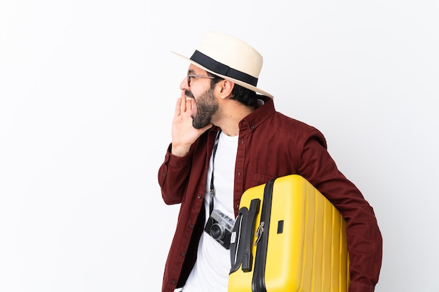 Traveler man man with beard holding a suitcase over isolated white wall shouting with mouth wide open to the lateral