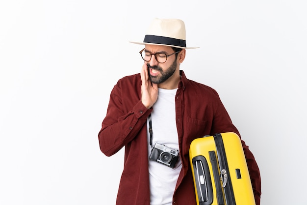 Traveler man man with beard holding a suitcase over isolated white wall with toothache
