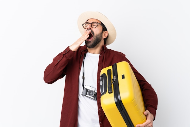 Traveler man man with beard holding a suitcase over white yawning and covering wide open mouth with hand