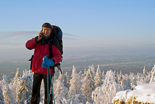 Traveler man at the mountain talking on a mobile phone in the background of a winter landscape