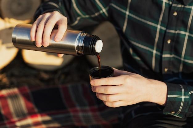 屋外の魔法瓶からホットコーヒーを注ぐ旅行者の男